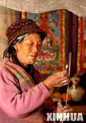 西藏尼木縣吞巴鄉吞達村藏族大媽嘎瑪正在點藏香