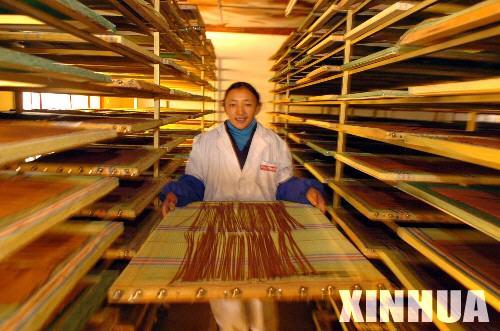 """藏族女工索朗卓瑪在拉薩知名藏香品牌""""敏竹梅芭""""廠內將干燥定型的藏香送往包裝車間。"""