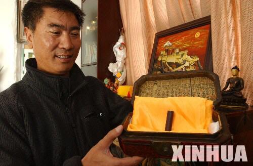"""拉薩知名藏香品牌""""敏竹梅芭""""廠董事長江措在展示他珍藏的一段具有千年歷史的藏香。"""