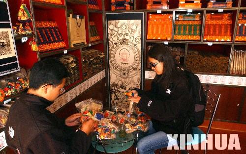 """游客在拉薩八廓街一藏香店鋪里挑選""""藏香包"""""""