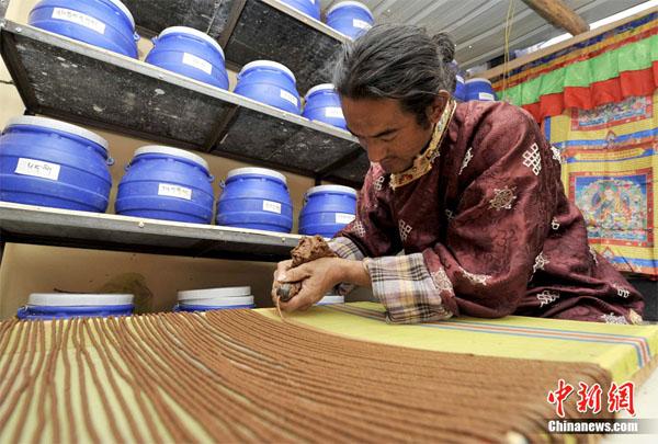 藏香师仁青德哲在工坊里用牛角挤制藏香 中新社发 李林 摄