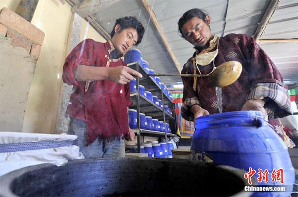 藏香师仁青德哲(图右)在工坊里精心熬制药材 准备制作藏香 中新社发 李林 摄